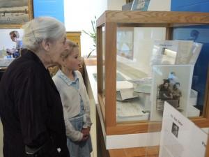 """Twee generaties kijken samen terug bij een vitrine over """"het kruis op de berg"""" op de tentoonstelling """"Bezet en bevrijd"""""""