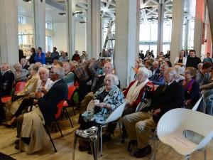 De bijeenkomst trok zo'n 200 belangstellenden. Vooraan met kopje koffie en blauwachtig bloemmotief Lotty Huffener-Veffer (93 jaar), wiens man Joep Huffener de mislukte aanslag pleegde met slachtoffer Philip de Leeuw. Links schuin achter haar (bij de betonnen pilaar) Jan Derk Boerma, wiens moeder tegelijk gevangen zat met de slachtoffers Philip de Leeuw en Pieter ter Beek.