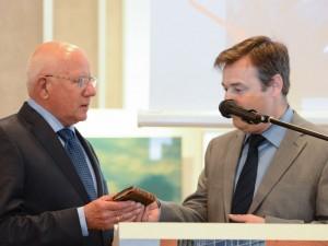 """Constant van den Heuvel overhandigt Teus van Manen het zakbijbeltje van slachtoffer ds. B.J. Ader dat enige tijd te zien was bij de expositie """"Het kruis op de berg"""" in Museum Veenendaal."""