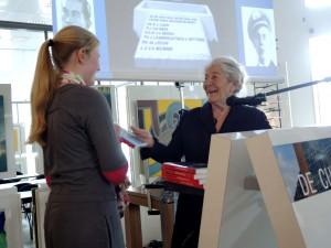 Betty Bausch-Polak (96 jaar), weduwe van slachtoffer Philip de Leeuw, reikt een boek uit aan Annemarie Loof (HAVO 3)