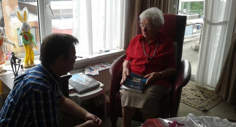 """Tantje Kuiper-Bruins in haar appartement in Nieuw-Beerta met op haar school """"Het kruis op de berg"""". Ze was zeer opgetogen over de hernieuwde belangstelling voor het monument tussen Rhenen en Veenendaal."""